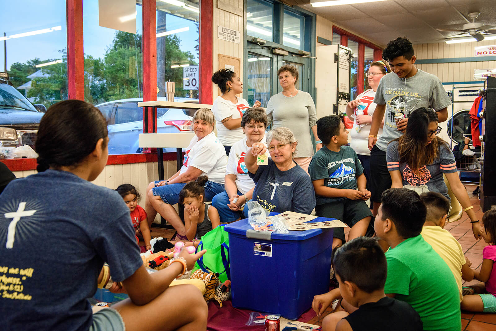 Volunteers from St. Paul Lutheran Church, San Antonio, hold a mini Sunday school lesson for children at August's Laundry Love event.